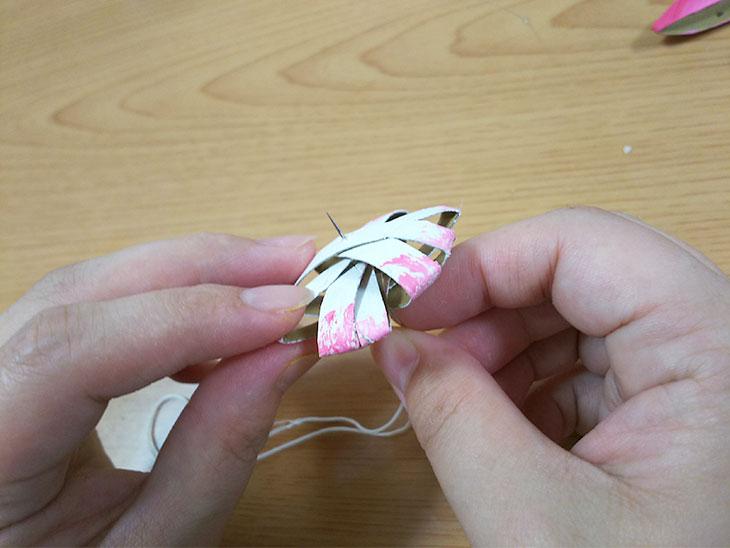 カットしたラップの芯を5つ重ねた中央に針で糸を通す様子