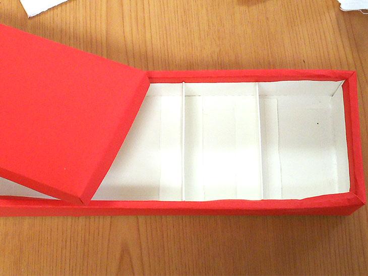 両面テープで仕切りを貼り付けた空き箱の写真