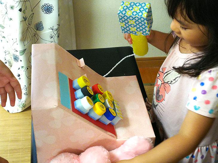 完成したレジスターのおもちゃで幼児が遊んでいる写真