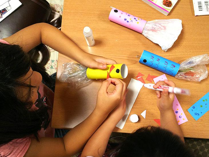 トイレットペーパーの芯に色紙を張って模様を描いて魚を作る女の子
