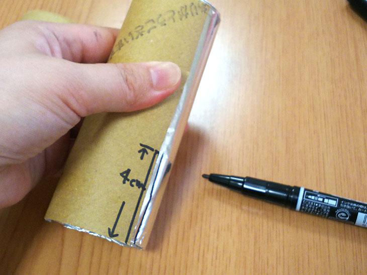 アルミホイルを巻いたトイレットペーパーの芯に、半分に切ったトイレットペーパーの芯を使って印をつける