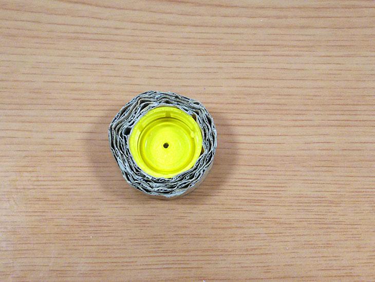 ペットボトルキャップにリボン状のダンボールを巻く