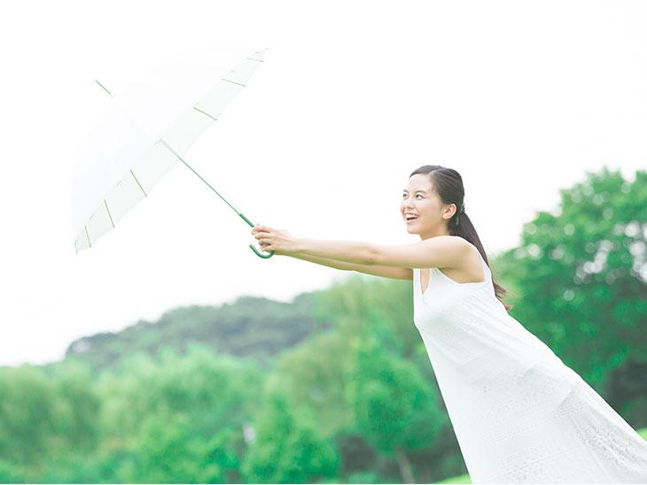 日傘をさす白いワンピースを着た女性