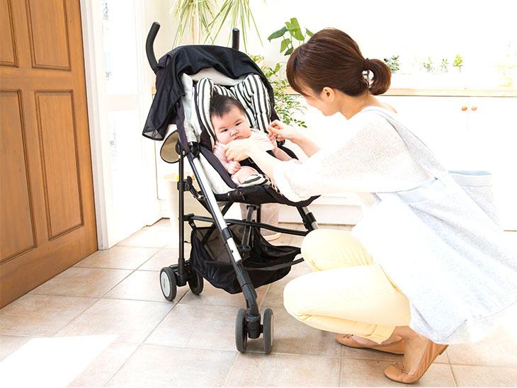 赤ちゃんをベビーカーに乗せる母親
