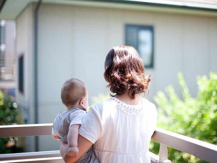 ベランダから外を眺めるお母さんと赤ちゃん