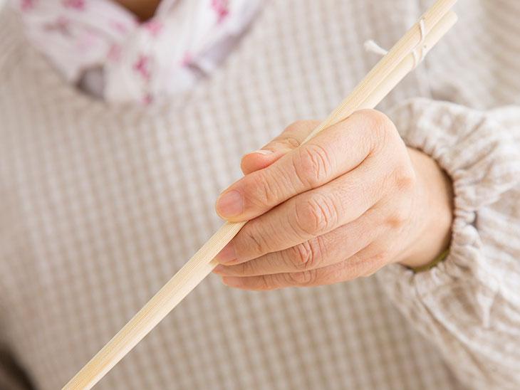 菜箸を持つシニア女性の手