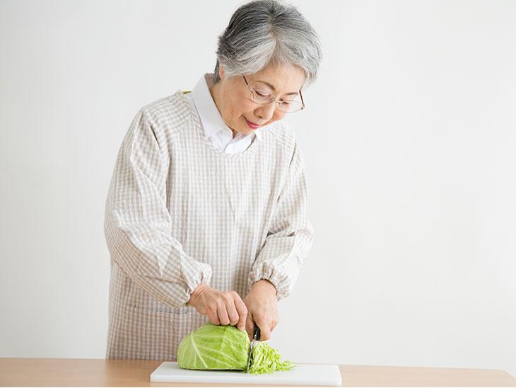 キャベツを切るシニア女性