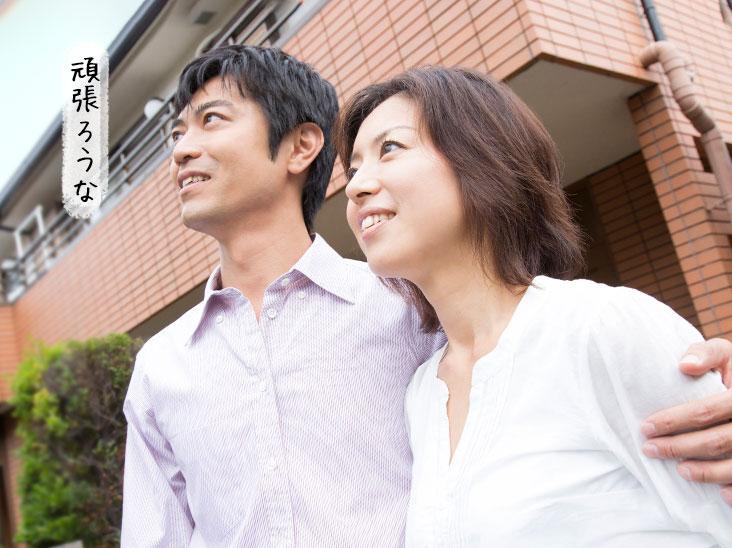 家の前で肩を抱き合ってる笑顔の夫婦