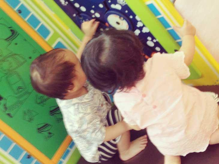 保育園で女の子と一緒に大きなおもちゃで遊んでる男の子