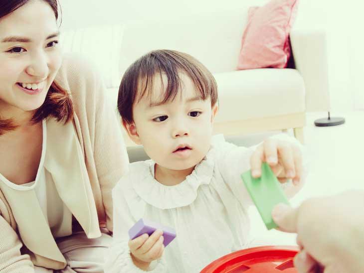 遊んでるおもちゃをパパに貸してあげる男の子を見て笑顔のママ