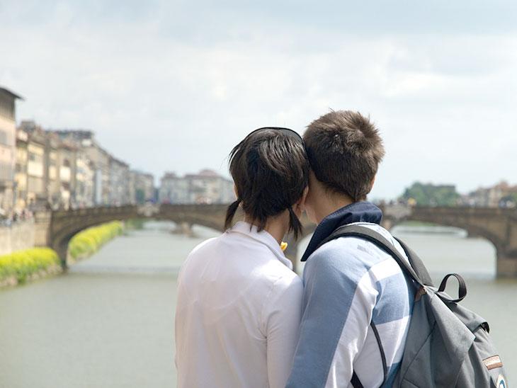 橋を見る若いイタリア人カップル