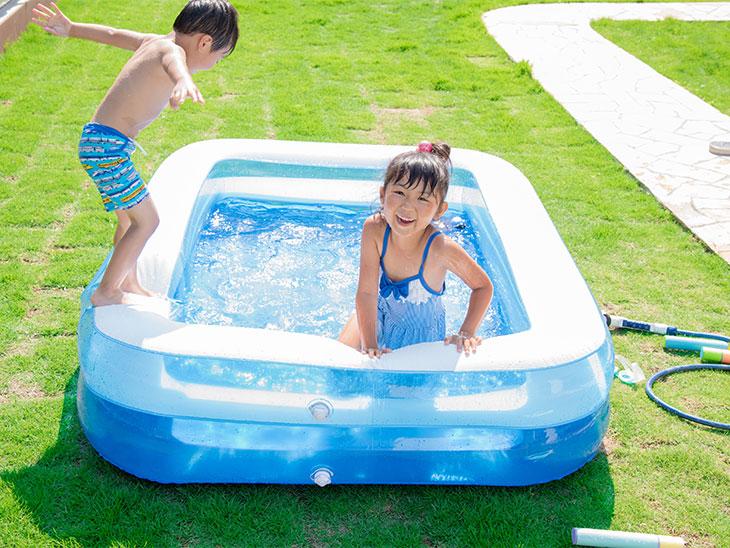 庭に出した家庭用プールで遊ぶ子供