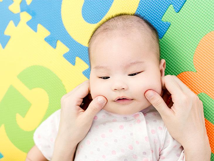 赤ちゃんのほっぺを触るママの手