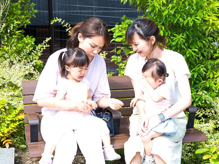 子供を抱いてベンチに座って話をしてるママ友
