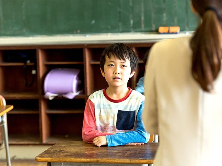 先生の後ろ姿と座る子供