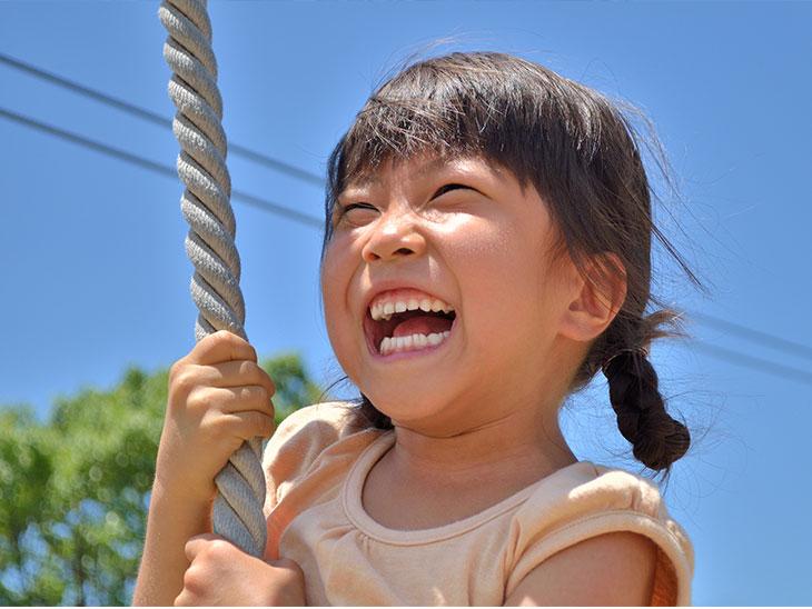 公園のターザンロープで遊ぶ女の子