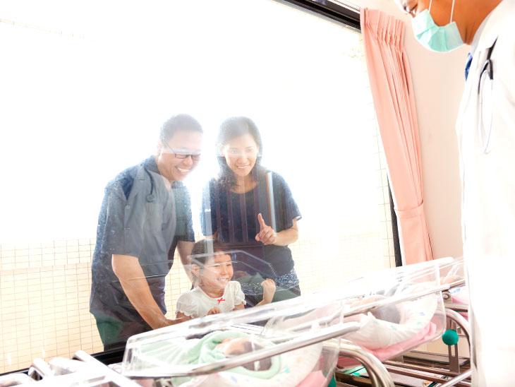 窓ガラスから生まれたての赤ちゃんを見る家族