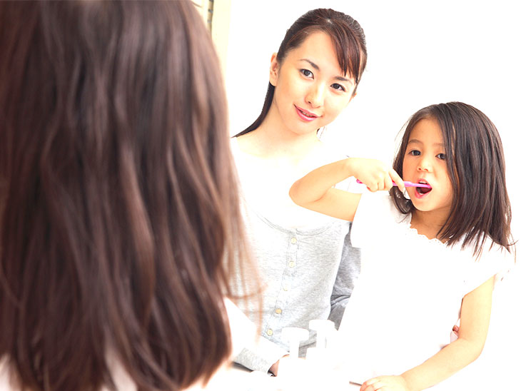 歯磨きをする女の子と見守る母親