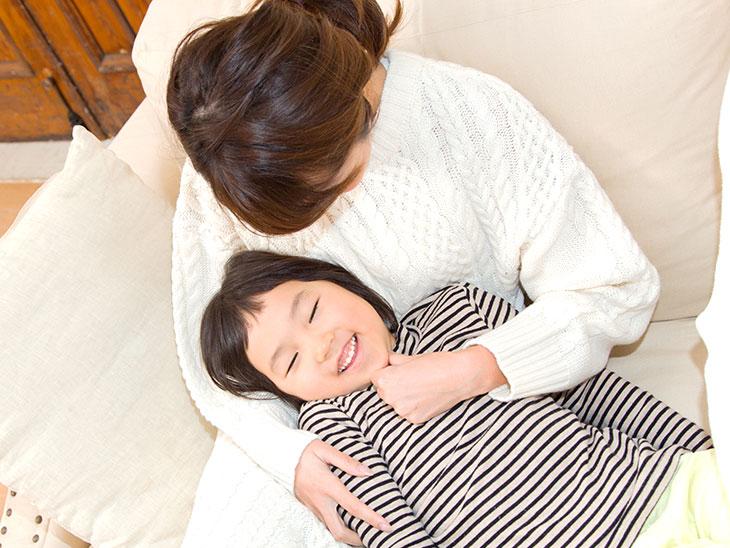 ソファで遊ぶ母親と子供の様子