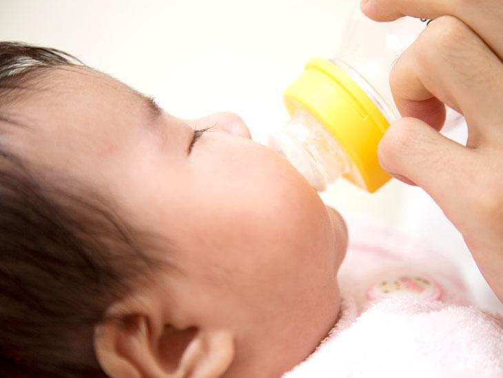 哺乳瓶からミルクを飲む女性