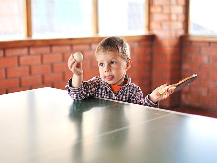 ラケットとボールを持って卓球台の前に立つ小さい男の子