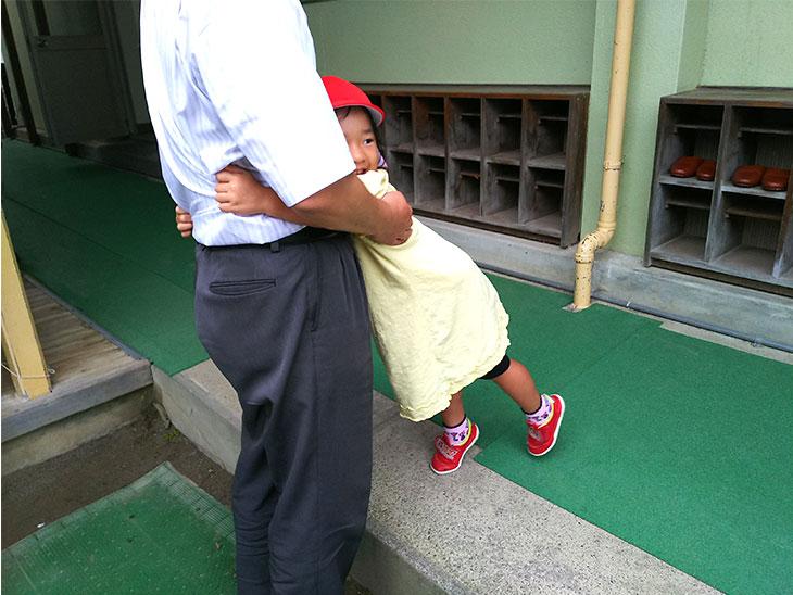 保育園で別れ際に父親にすがりつく園児