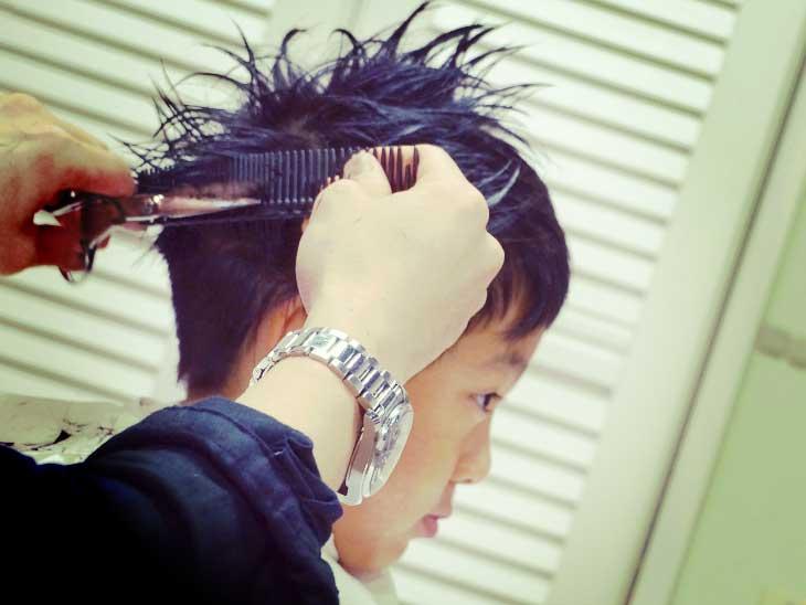 美容室で髪を切ってもらってる男の子