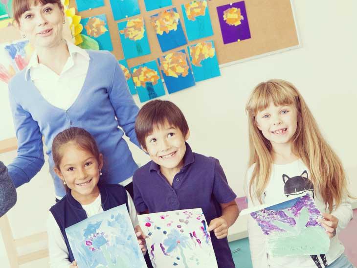 描いた絵を見せてる園児と笑顔の保育士