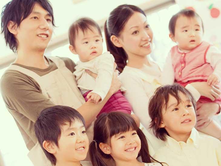 子供に囲まれてる男性保育士と女性保育士
