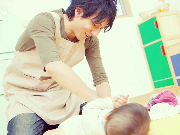 赤ちゃんのオムツ交換をしてる男性保育士