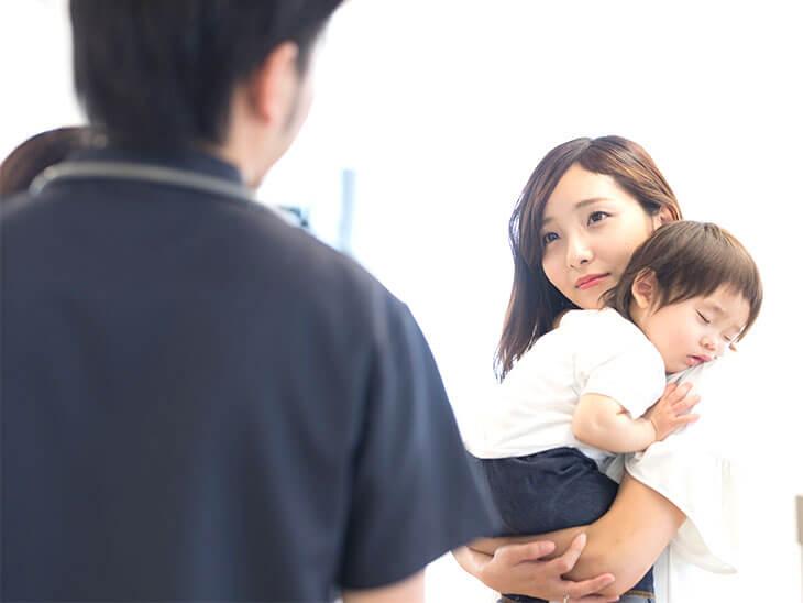 小児科で男の子を抱っこする母親