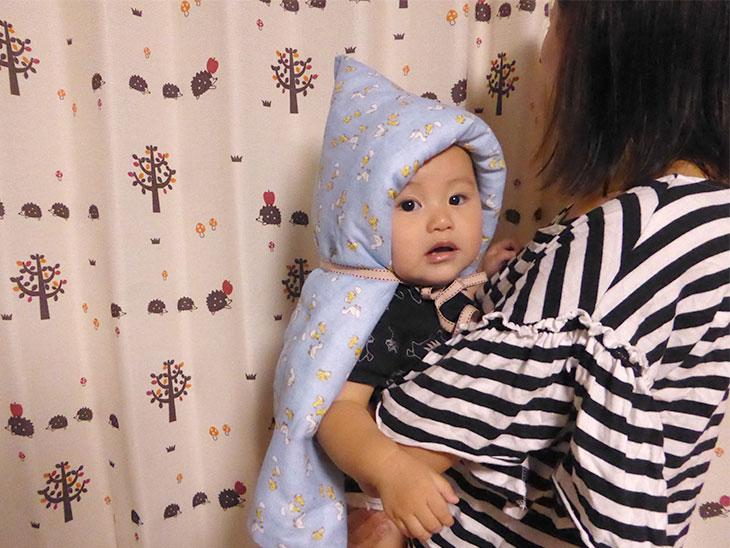 母親に抱かれる防災頭巾をつけた赤ちゃん