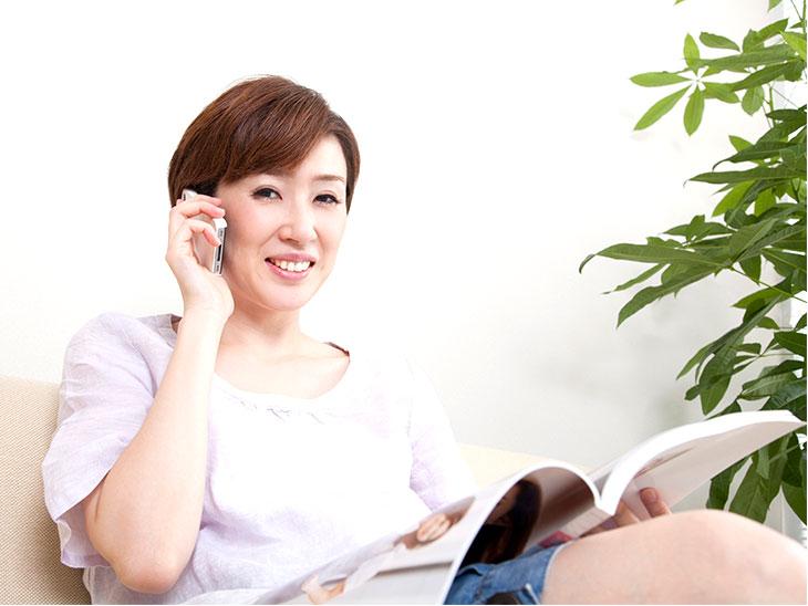 雑誌を見ながら電話する主婦