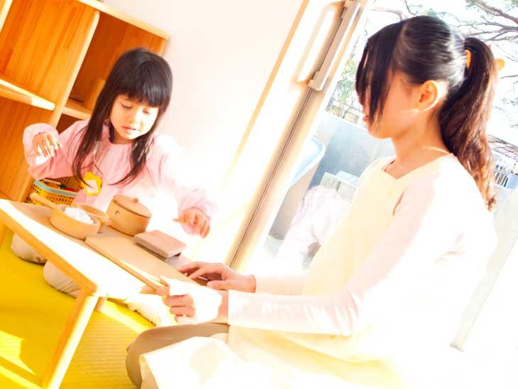 幼稚園でお店やさんごっこ遊びをしてる女の子と保育士