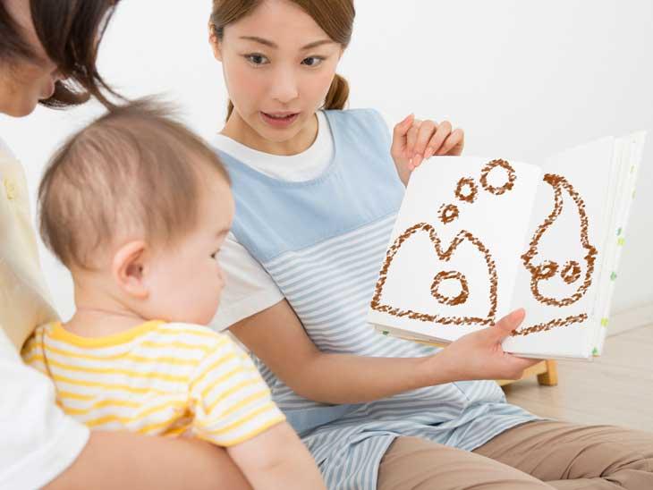 幼児に絵本の読み聞かせをしてる保育士