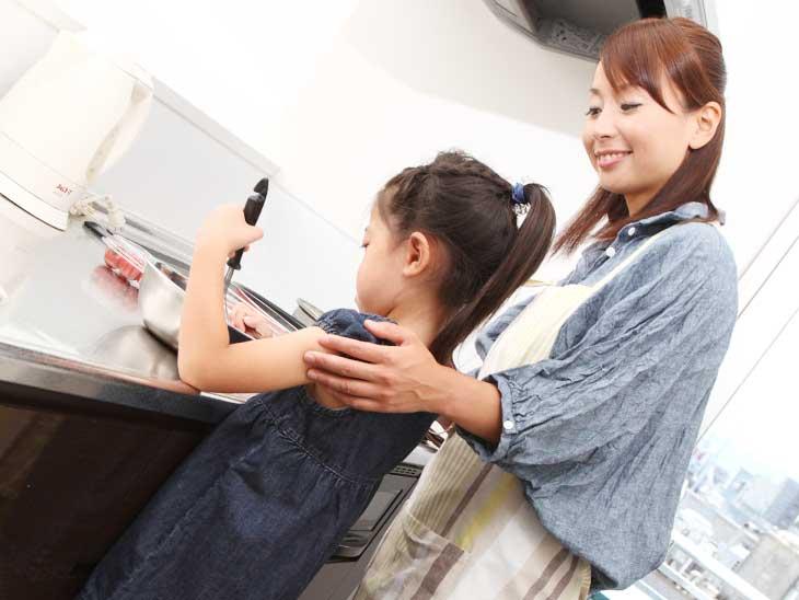 キッチンで母親の料理の手伝いをしてる女の子