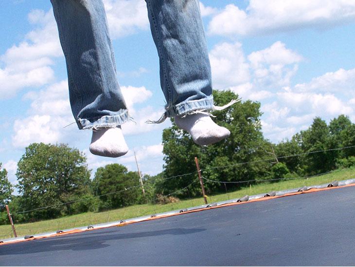 トランポリンで飛ぶ人の足