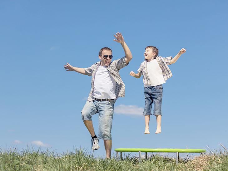 お父さんと一緒にトランポリンで遊ぶ男の子