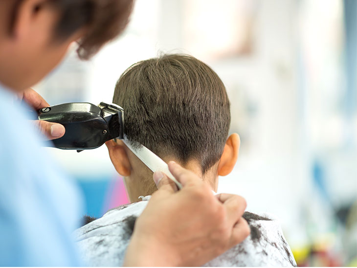 床屋さんで髪を切ってもらってる男の子