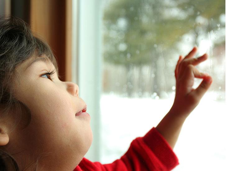 窓から雨が降ってる外を見る女の子
