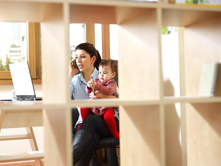 赤ちゃんを抱っこしながら電話する母親