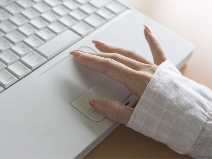 ノートパソコンを操作する女性の手