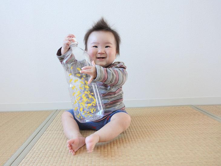 マカロニが入ったペットボトルで遊ぶ赤ちゃん