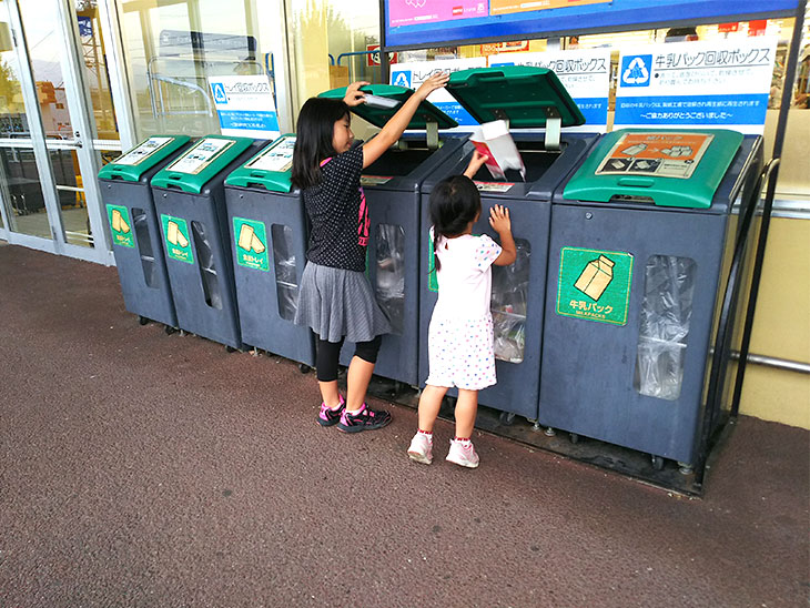 スーパーに設置されたリサイクルボックスに資源を入れる姉妹