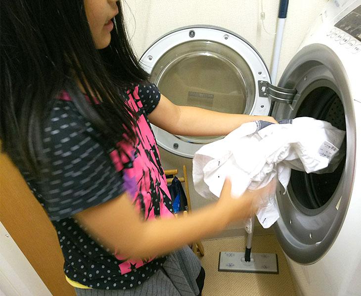 洗濯機に洗濯物を入れる女の子