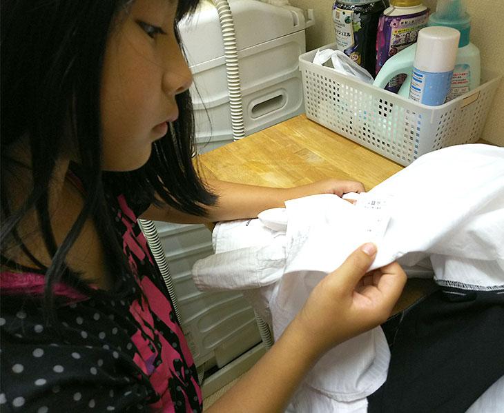 シャツの洗濯タグを確認してる女の子