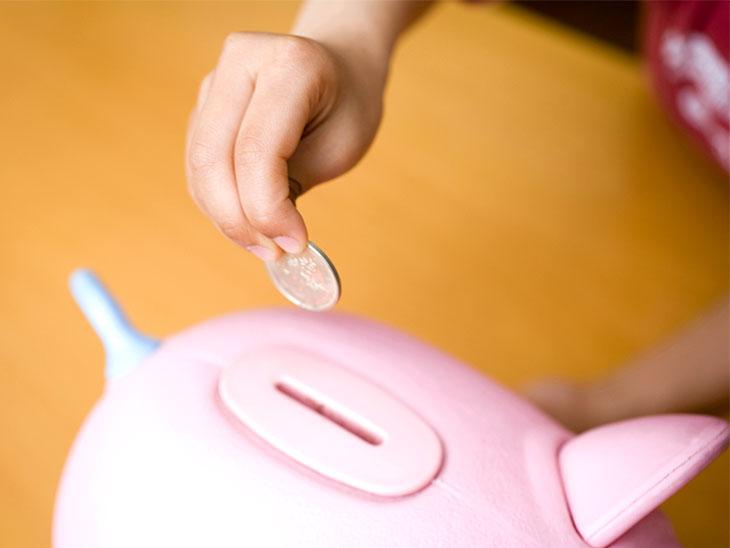貯金箱にお金を入れようとしている子供の手