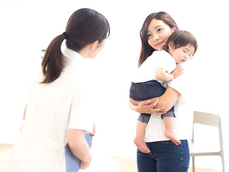 看護師さんと話す園児を抱っこしながら母親