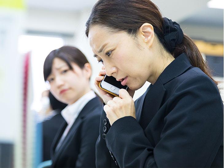 電話対応をする女の人