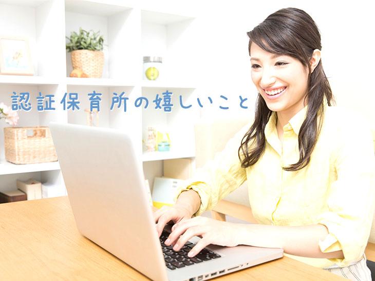 嬉しい表情でノートパソコンを操作する女性